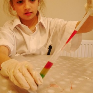 a girl making a liquid rainbow with letterbox lab science equipment