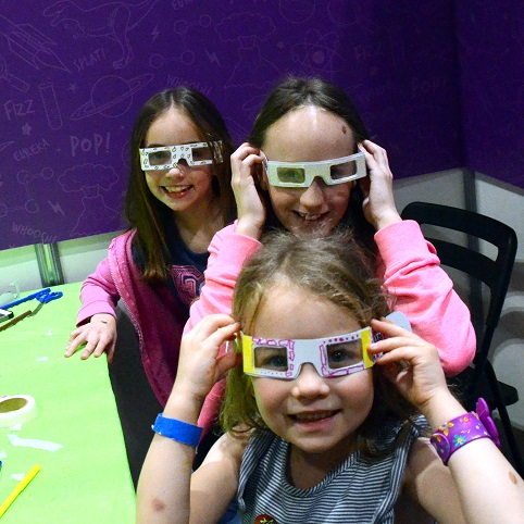 3 girls wearing letterbox lab's rainbow glasses from their first science kit