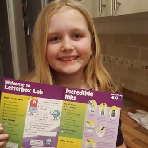 a girl holding up the instruction book for letterbox lab's explore box